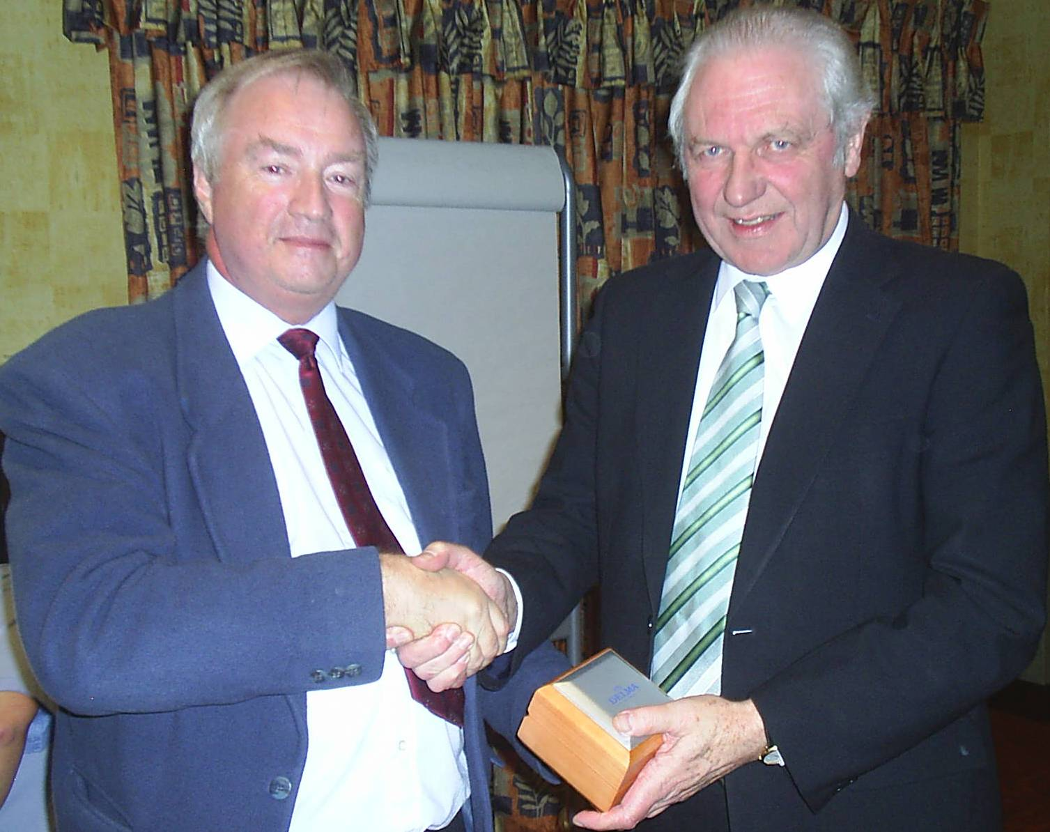Jim Shaw receiving a watch from Robert Haworth