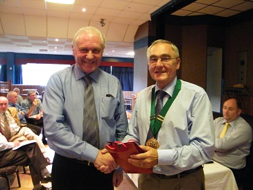 Jim Shaw receiving a momento from the new Chairman Terry Pateman