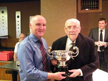 Jeffery Higgins receives the Logan Johnstone Cup  for the Malcolm Brodie Merit award from League President Herbie Johnstone.
