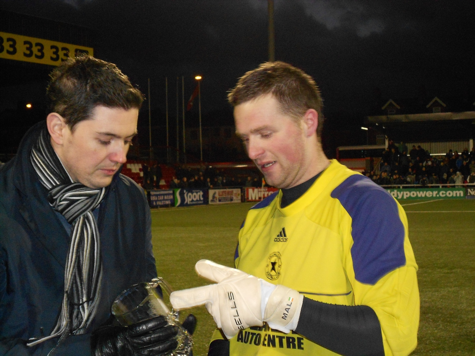 Mark Whyte (Daily Mirror) hands over Man of the Match award to the Crumlin Star Goalkeeper Malachy Thompson.