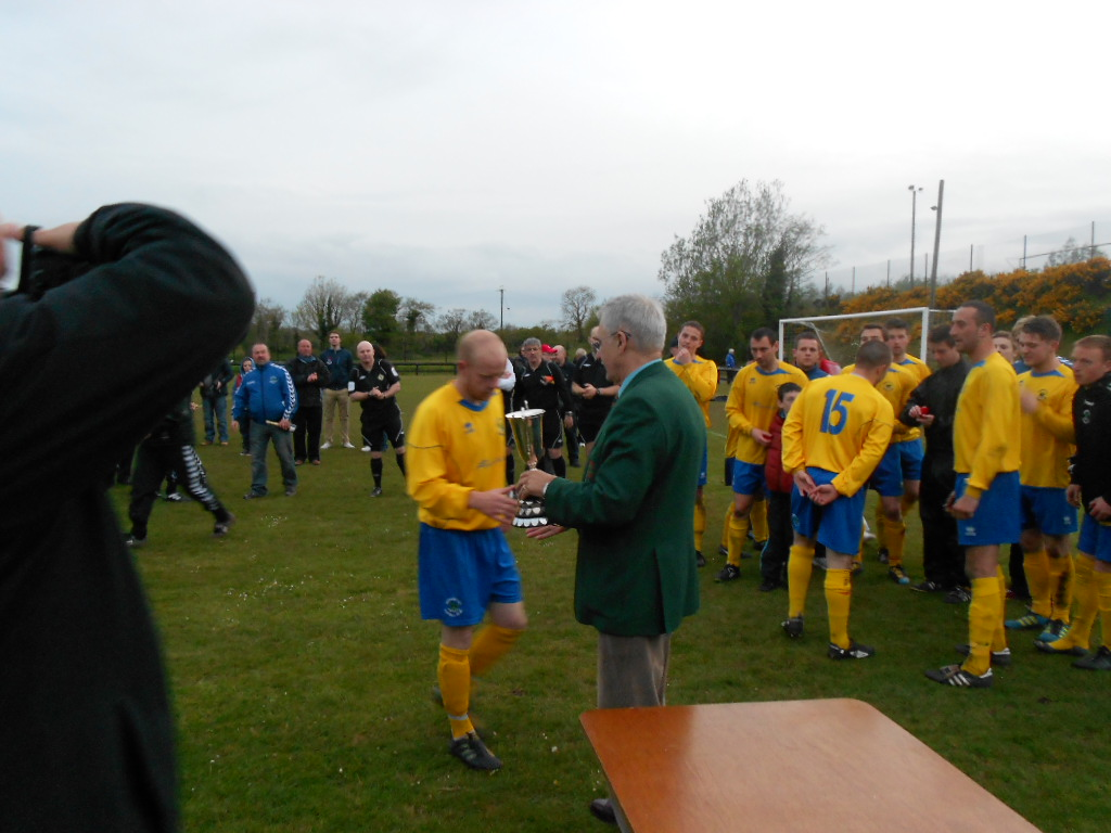 League Chairman T Pateman hands over the Clarence Cup to the Derriaghy captain